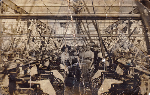 Workers amidst the looms in Oswaldtwistle textile mill, Oswaldtwistle, Lancashire. Decorated for the 1910 coronation.
