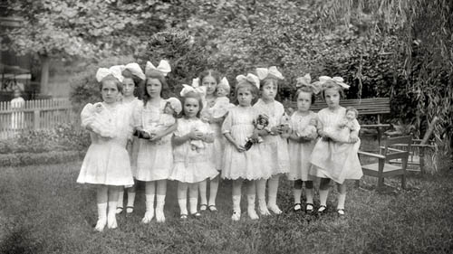 a black and white photo of a group of girls in dresses and hair bows standing outside