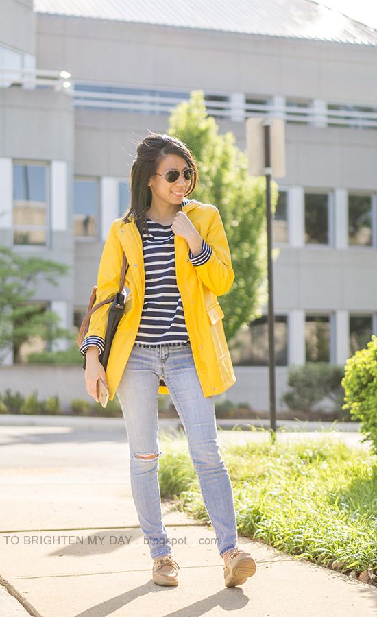 yellow rain jacket, striped top with pom poms, lightwash distressed jeans, boat shoes