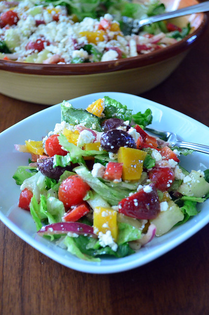 A small plate of Greek Salad with a serving bowl with more salad behind it.