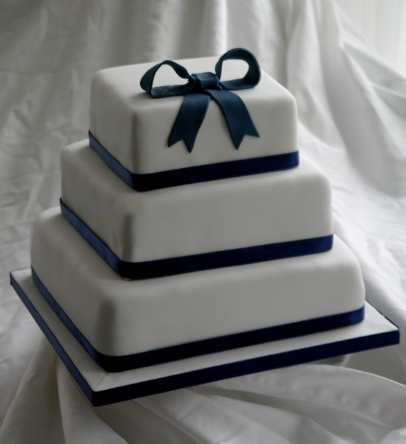Simple 3 tier square wedding cake with navy blue bow detail