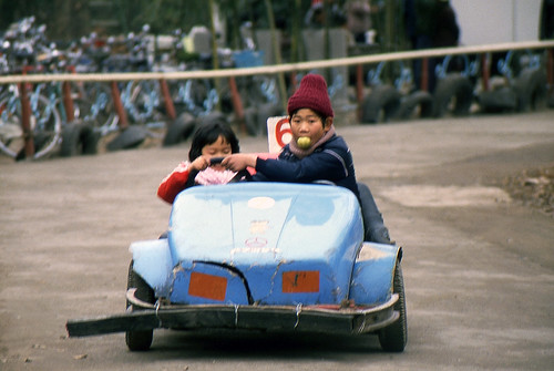 Big brother interfering with his sister driving a go cart