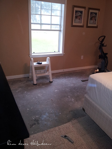 master bedroom with mustard gold walls and partially removed carpeting (before)