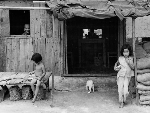 Vietnamese house, little girls standing outside, old man looking outside of window.