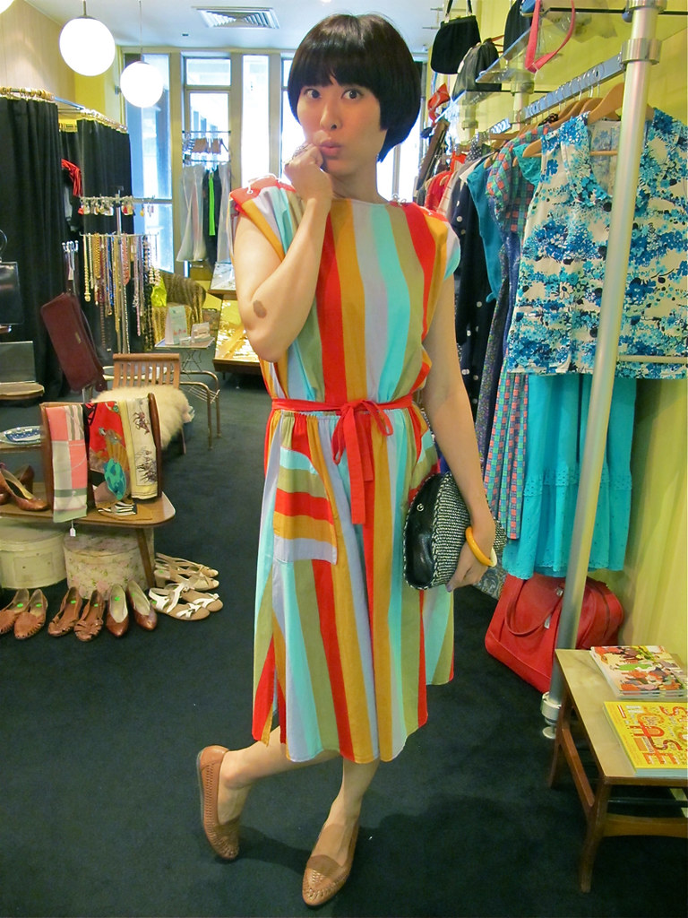X-Wen looks happy in this brightly-coloured candy striped dress, worn with a 1980s orange and white plastic bangle, 1980s brown leather sandals and a 1970s woven clutch bag.