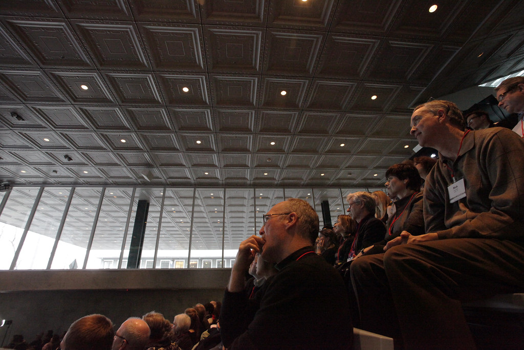 Alumni enjoying the Rem Koolhaas lecture in the Abby and Howard Milstein Auditorium. The view shows the auditorium ceiling and University Avenue cantilever.