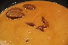 Añadimos la pasta de curry rojo en la salsa donde han cocido las cabezas y las pieles