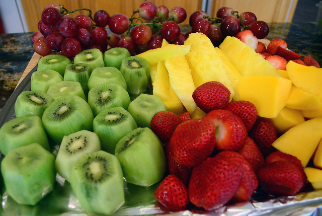 A tray covered in different cut up fruit.