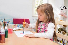 Little blonde girl painting with brush and water colours. (Misc)