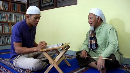 Aiman membaca al Quran sambil diperhatikan oleh ustaz