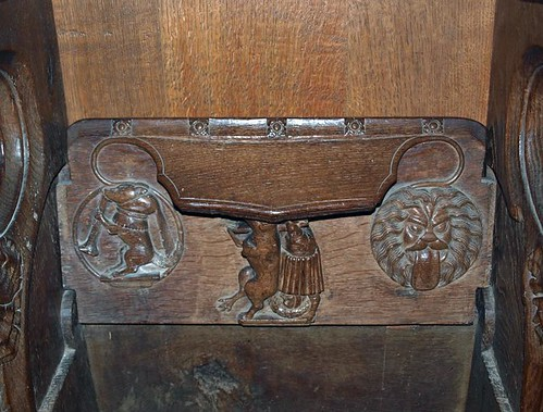 Misericord S5 Fox carrying a priest preceeded by a wolf blowing a trumpet & followed by a Lion's head with protruding tongue  (1)