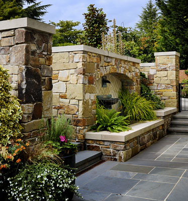 The water fountain and stone wall shelter the front entry of this home.