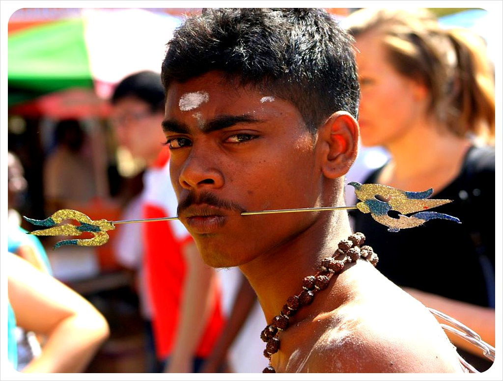 thaipusam man with spears through mouth