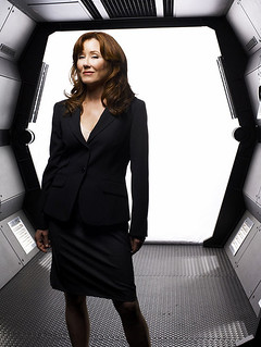 Laura Roslin, a white woman with brown hair, standing in a doorway