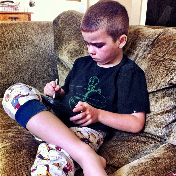 Sick kid and his iPad. Husband brought home stylus' for each of us this weekend. He only uses the stylus now.