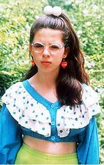 Bespectacled girl wearing red heart earrings and a floucy blue blouse.