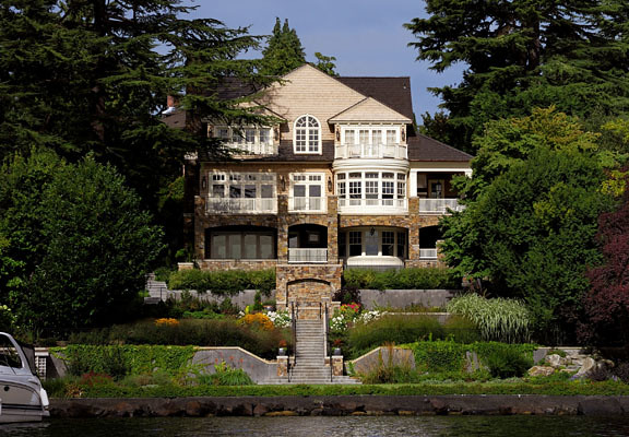Graceful stone terraces provide access to the lake from this large waterfront home.