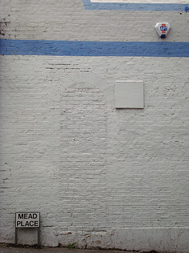 "A white-painted brick wall with light blue lines running across it above head-height.  The lines of the brickwork show that there was a narrow arch there which has since been bricked up.  A small street sign at ankle level reads ""Mead Place""."