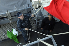 YOKOSUKA, Japan (Feb. 21, 2012) Quartermaster Seaman Rodger Weaver and Yeoman 3rd Class Randy Sarran hoist flags up the mast as U.S. 7th Fleet flagship USS Blue Ridge (LCC 19) departs Yokosuka, Japan. (U.S. Navy photo by Mass Communication Specialist 3rd Class Cale Hatch)