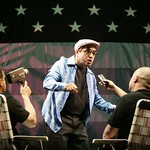 Richard Montoya (c.) as Miami theater publicist Charlie Cinnamon, who regales reporters with his stories of the old days on South Beach, in the Huntington Theatre Company's production of
