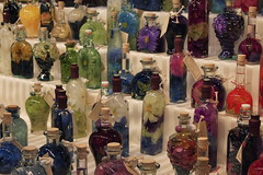 silk flowers inside bottles with oil as oil lamps