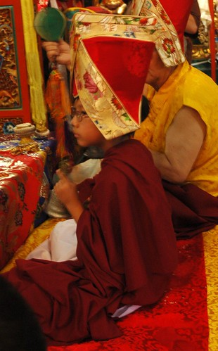 HE Asanga Sakya ringing a vajra handled bell during dedication prayers, wearing the sashu hat, his grandfather, His Holiness Jigdal Dagchen Sakya, playing a damaru, both of Seattle, Washington, Sakya Lamdre, Tharlam Monastery, Boudha, Kathmandu, Nepal by Wonderlane
