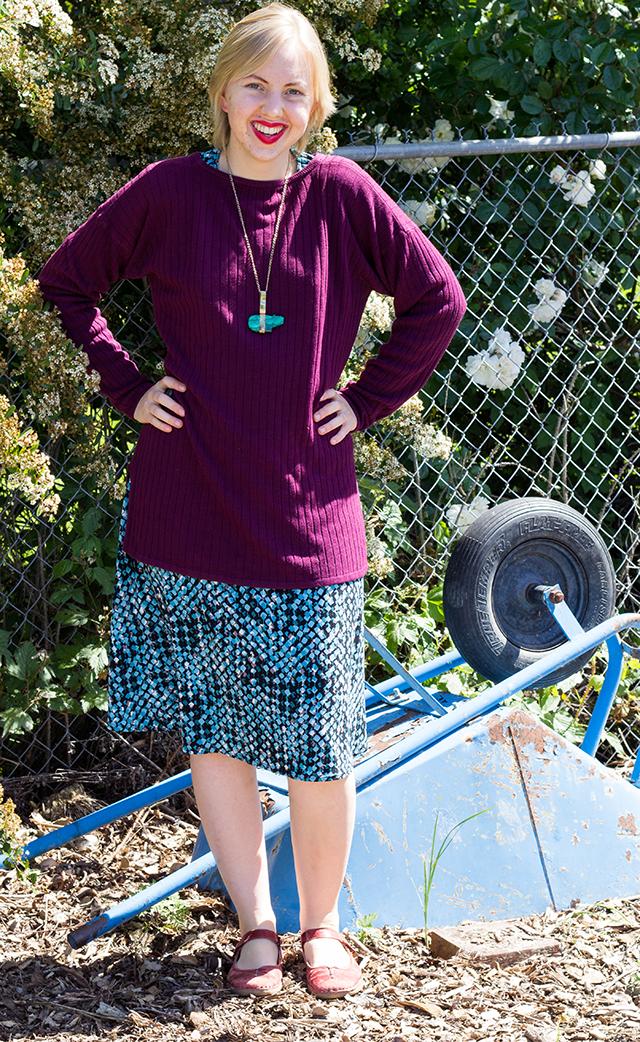 plum purple sweater, green pendant, green patterned dress, overturned blue wheelbarrow in the garden