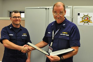 NEW ORLEANS - U.S. Coast Guard Commander Scott Saunders (left), receives the Coast Guard Commendation Medal from U.S. Coast Guard Captain Thomas Sparks (right), Federal On-Scene Coordinator of the Deepwater Horizon Response, May 1, 2014. Saunders served as the deputy FOSC during his deployment to the response.