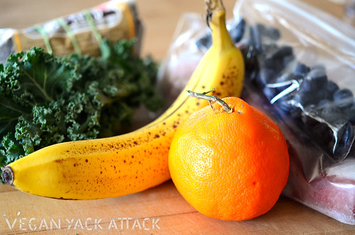 Kale, banana, orange, blueberries, and other raw smoothie ingredients.