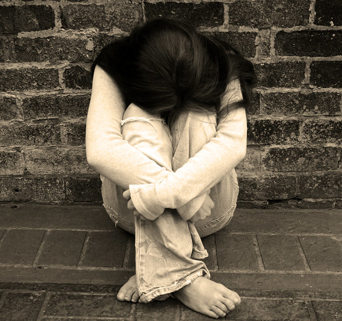 A girl leaning against a brick wall looking sad and alone