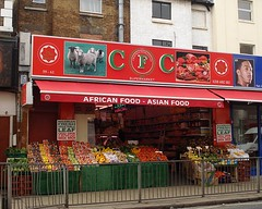"A terraced shopfront with a red sign reading ""CFC Supermarket"".  The words ""Croydon Food Centre"" are written in small in a circle around the ""F"".  There's also a picture of a sheep, and another picture of cuts of meat.  On each side of the sign is a star with the word ""Halal"" in both English and Arabic.  The awning is also red, and reads ""African Food — Asian Food"".  The shopfront is open, and there's a colourful display of vegetables at the front."