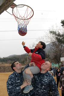 BUSAN, Republic of Korea (Feb. 25, 2012) Yeoman 3rd Class Jesse Welsh, left, and Interior Communications Electrician 2nd Class Sidney Hendrickson of 7th Fleet command ship USS Blue Ridge (LCC 19) play basketball with a Korean child during a community service project. (U.S. Navy photo by Mass Communication Specialist 2nd Class Timmy Wakefield/)