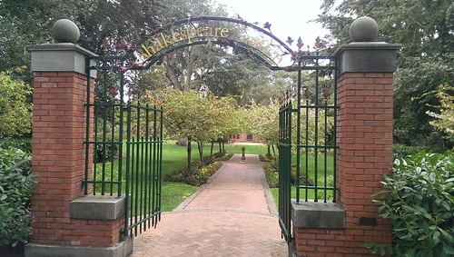 Brick and wrought iron gate with an arch with the words Shakespeare Garden