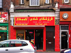 "A terraced shopfront in bright red.  The faux stone wall from the previous photo is still there but has been painted the same bright red almost but not all of the way up.  ""Shadi Market"" is written in bright yellow above the shopfront.  A decal on the window reads ""FRESH NAAN & CHAPATI [F]OR £1""."