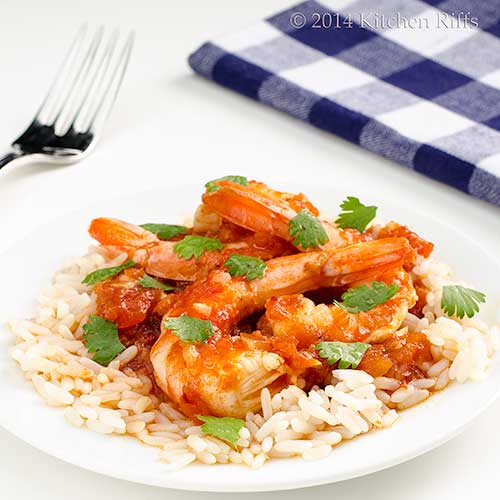 Shrimp in Chipotle Sauce with cilantro garnish on plate, with fork and napkin in background