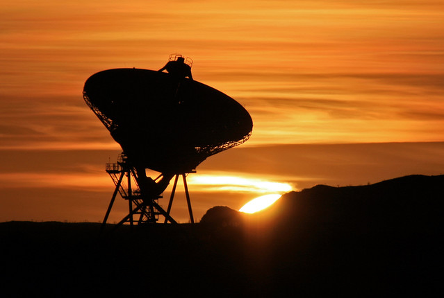 New Mexico sunset behind an 82-foot-diameter radio telescope at Los Alamos National Laboratory (Technical Area 33) – one of 10 in the Very Long Baseline Array spanning 5,351 miles.  Photo by Ethan Frogget.