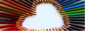 An array of pencil crayons in rainbow hues, arranged with their tips facing inward to form a heart