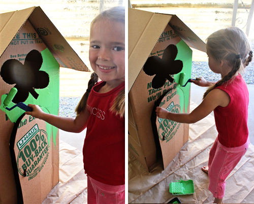 child painting cardboard house