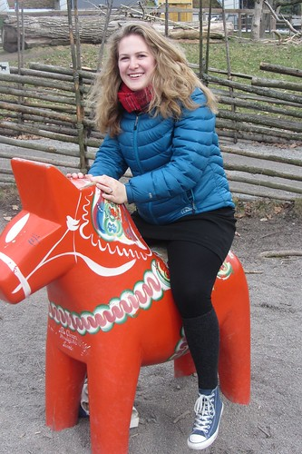 Outdoors, a woman sits on a colorful sculpture of a horse