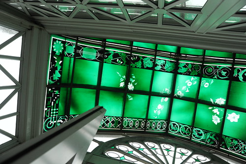 Complex design of the 100 year old green white and black stained glass window in the Seattle Volunteer Park Conservatory, Capitol Hill, Seattle, Washington, USA