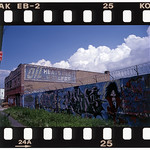 "Frank Jump coined the term 'ediglyph' to describe fading ads and graffiti. It's combination of the word 'edifice' and 'petroglyph,' an ancient wall carving.   Jump photographed this ad on White Plains Road in the Bronx in 1997. He notes that often the old ads remain untouched by modern graffiti taggers. ""Where the two works of art collide -- the ancient painted message of a long deceased commercial artist and the cryptic message or cartoon image of a spray paint artist -- a uniquely significant ediglyph is created.""   Photo by Frank Jump."
