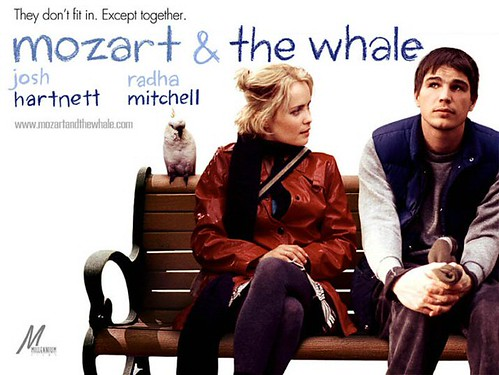 A poster for Mozart and the Whale: Josh Harnett and Radha Mitchell sit on a park bench together.