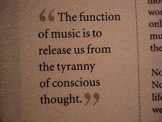 "A picture of a yellowed page on which is typed ""the function of music is to release us from the tyrrany of conscious thought"""