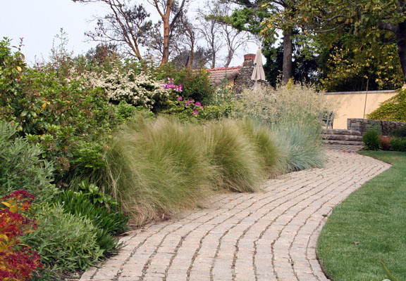 This granite path is bordered by grasses and lawn.