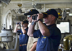 Capt. Mark Benjamin, commanding officer of USS Frank Cable (AS 40) looks through binoculars on the bridge as the ship deaprts Guam March 14. (U.S. Navy/MC3 Jon Erickson)