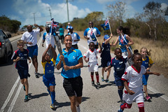 Football coach Sonia Bien-Aime escorted by young football players relay the Queen's Baton, in Grace Bay, Turks and Caicos Islands, Wednesday 16 April 2014. Turks and Caicos Islands is nation 56 of 70 nations and territories the Queen's Baton will visit....