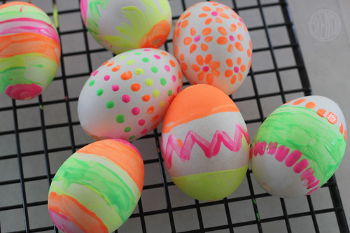 painted eggs drying on a rack