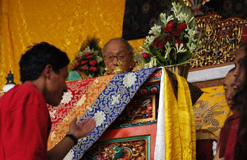 HH Dagchen Rinpoche overseeing the long life initation from his throne, a Tibetan man requests the blessing, two monks, Sakya Lamdre, Tharlam Monastery stage, Boudha, Kathmandu, Nepal by Wonderlane