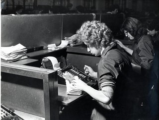 Clearing Department, woman sorting cheques and using adding machine - 1960s