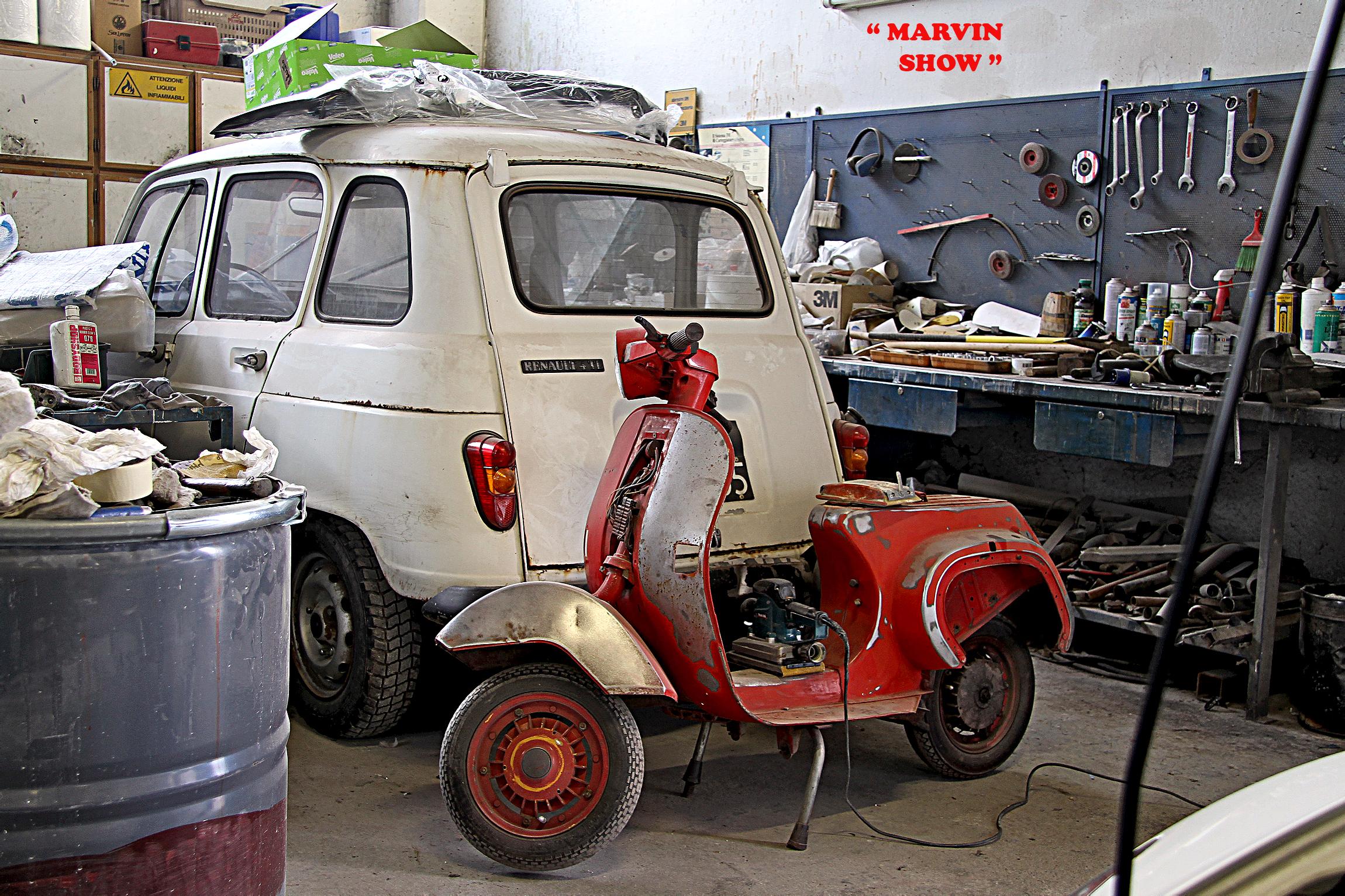 Renault 4 et Vespa appuyée sur son coffre dans garage vintage
